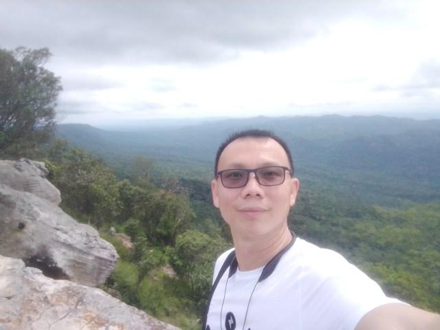 ภาพถ่ายเซลฟี่ของผู้ชายใส่แว่นสีชา เสื้อสีขาว ณ ริมผาสุดแดนดิน จ.ชัยภูมิ