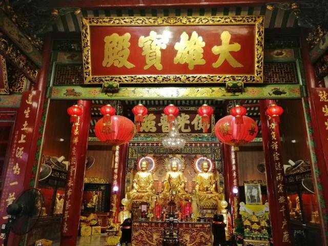 ภาพถ่ายภายในศาลเจ้าจีน มีพระพุทธรูปสามองค์อยู่ด้านหน้าโต๊ะบูชา มีตัวอักษรจีนบนป้ายใหญ่ๆ อยู่ด้านบน