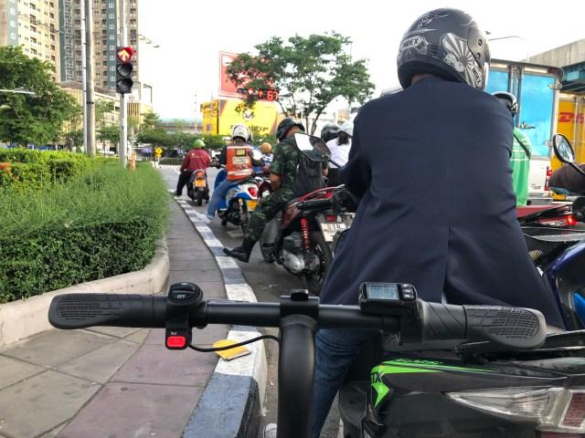 ภาพของแฮนด์จักรยานไฟฟ้า ขณะจอดติดไฟแดงอยู่ตรงทางแยก ต่อท้ายจักรยานยนต์อีกหลายคัน
