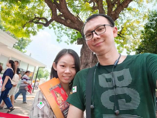 ภาพเซลฟี่ของผมใส่เสื้อสีเขียว กับแฟนที่ถือแผ่นพับของงานนิทรรศการอยู่