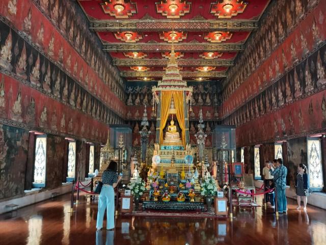 ภาพของพระอุโบสถ ที่มีพระพุธรูปประดิษฐานอยู่ตรงกลางโถง มีผู้คนกำลังถ่ายรูปอยู่