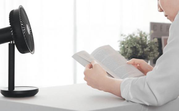 ผู้ชายใส่เสื้อเชิ้ตแขนยาวสีขาวกำลังอ่านหนังสือ โดยมีพัดลม Xiaomi Youpin SOLOVE F5 สีดำอยู่ด้านซ้ายมือ