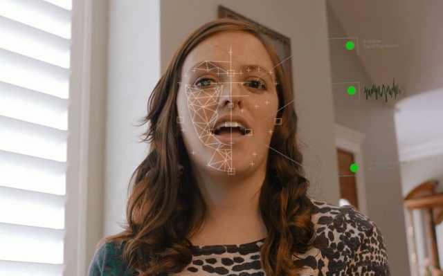 ผู้หญิงผมสีน้ำตาลยาว มีกราฟิกของการตรวจสอบใบหน้าแสดงอยู่บนใบหน้าด้วย