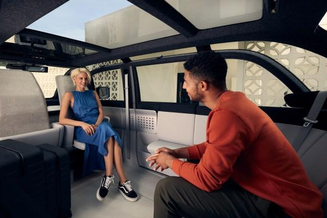 ผู้หญิงใส่ชุดกระโปรงยาวสีน้ำเงิน กำลังพูดคุยกับผู้ชายในชุดเสื้อแขนยาวสีส้ม กางเกงสีน้ำตาล