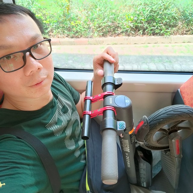 ภาพของผมกำลังนั่งอยู่บนรถเมล์ ใส่เสื้อสีเขียว มีสกู๊ตเตอร์ไฟฟ้าตั้งอยู่ด้านหน้า