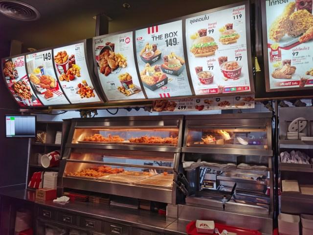 ภาพในร้าน KFC ตรงเคาน์เตอร์ ที่แสดงรายการอาหาร และมีตู้เก็บไก่ทอดอยู่