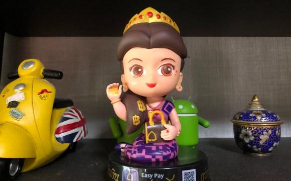 ตุ๊กตานางกวักแม่มณีของธนาคารไทยพาณิชย์ และมีรถมอเตอร์ไซค์จำลองแบบเวสป้าสีเหลืองอยู่ทางด้านซ้ายของรูป และด้านขวาของรูปมีถ้วยเซรามิกสีน้ำเงิน ลายดอกไม้