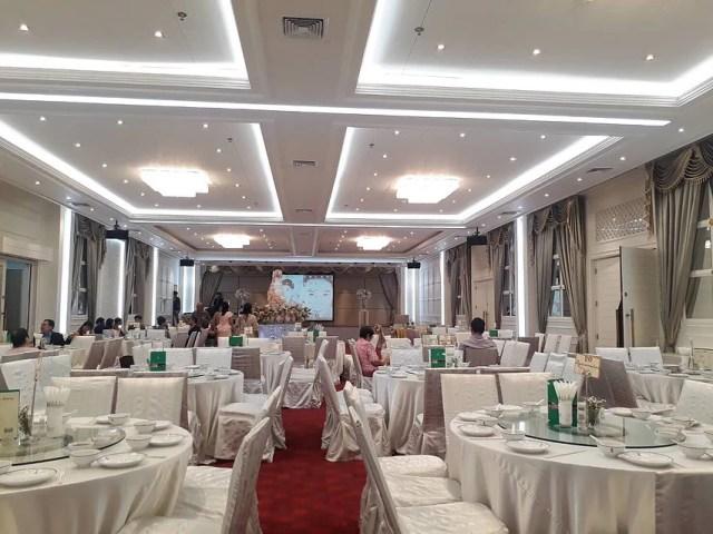 ภาพของห้องจัดเลี้ยงแต่งงาน ที่มีโต๊ะจีนสีขาววางเรียงรายอยู่