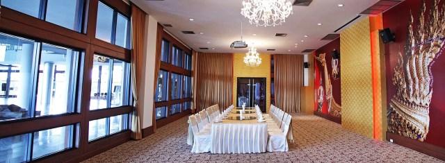 ภาพมุมกว้างของห้องประชุม ที่มีการจัดเรียงโต๊ะและเก้าอี้สีขาวอยู่ตรงกลางห้อง ด้านขวาเป็นวอลล์เปเปอร์ลายเรือสุพรรณหงส์
