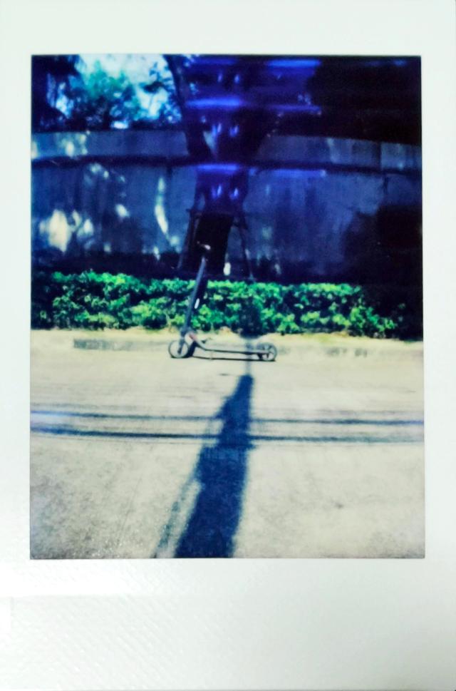 ตัวอย่างภาพถ่ายด้วยกล้อง Escura Instant 60s เป็นภาพระยะไกลของสกู๊ตเตอร์ไฟฟ้า ที่จอดอยู่ริมถนนในสวน
