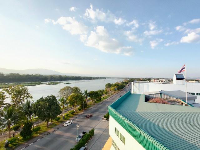 วิวนอกหน้าต่างโรงแรม เห็นถนน แม่น้ำปิง และหลังคาอาคารต่างๆ