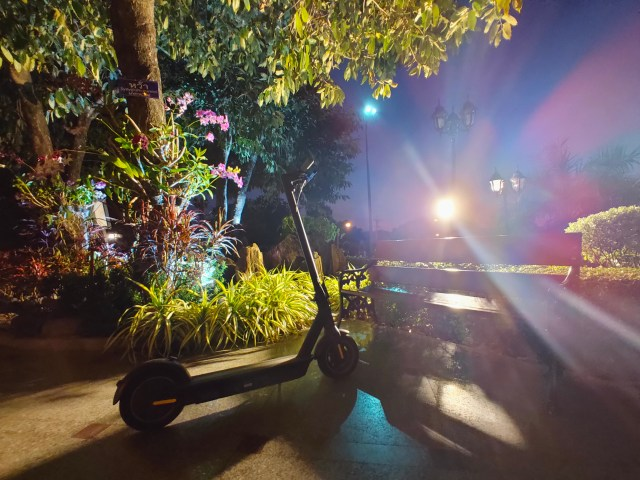 ภาพของสกู๊ตเตอร์ไฟฟ้าที่จอดอยู่ โดยมีแบ็กกราวด์เป็นม้านั่งยาว และต้นไม้ ยามค่ำคืน