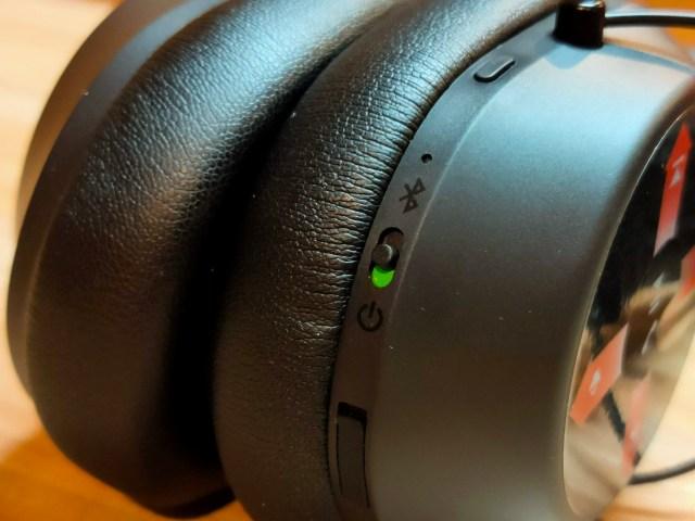 ภาพโคลสอัพของหูฟัง Plantronics BackBeat FIT 6100 มีสวิตช์เปิดปิดและเข้าสู่โหมดจับคู่อุปกรณ์ และปุ่มสำหรับเปิดฟีเจอร์ Open-mic และฝาปิดพอร์ต Micro USB