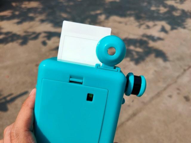 กล้อง Escura Instant 60s ที่หมุนเอาฟิล์มรูปออกมาแล้ว