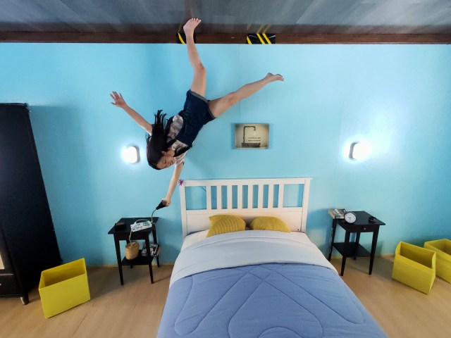 ภาพของห้องนอน มีเตียงอยู่กลางห้อง ผนังห้องสีฟ้า มีผู้หญิงกำลังยืนกลับหัวอยู่