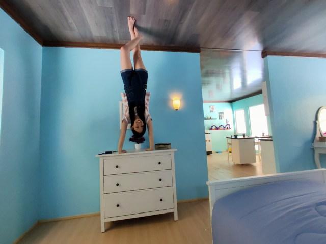 ภาพภายในห้องผนังสีฟ้า ที่มีผู้หญิงกำลังยืนกลับหัว โดยใช้มือยันโต๊ะลิ้นชักสีขาวอยู่