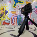 กล้อง GoPro Hero 8 Black บนขาตั้งสามขาขนาดเล็ก วางอยู่บนพื้น มีแบ็กกราวด์เป็นกำแพงที่มีภาพกราฟิกต่างๆ อยู่