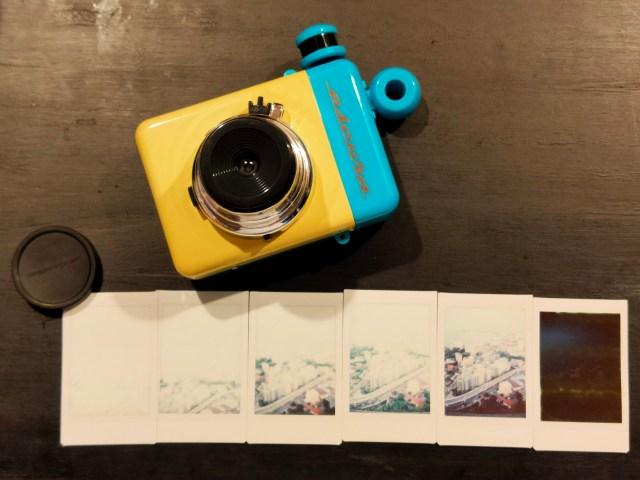 กล้อง Escura Instant 60s และฟิล์มที่ถ่ายภาพแล้ว 6 ใบ เรียงตามลำดับความสว่างของภาพที่ถ่าย