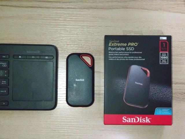 ภาพส่วนหนึ่งของคีย์บอร์ดไร้สาย Microsoft ที่มีตัว SanDisk Extreme Pro Portable SSD 1TB และกล่องใส่ วางอยู่ข้างๆ
