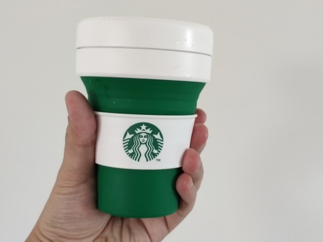 มือข้างซ้ายกำลังถือแก้ว Starbucks x Stojo สีเขียวอยู่