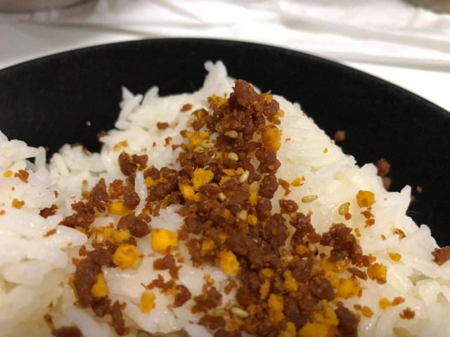 ส่วนหนึ่งของจานข้าวสีดำ ที่มีข้าวสวยตักวางอยู่ โดยมีผงโรยข้าวรสไก่และไข่ สีน้ำตาลในส่วนที่เป็นไก่และผสมกับสีเหลืองในส่วนที่เป็นไข่ โรยอยู่