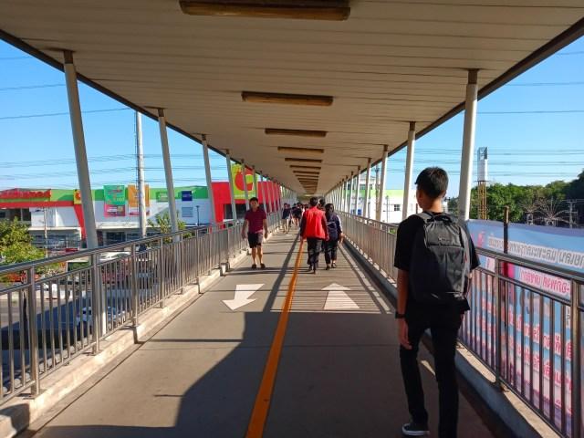 สะพานลอยที่มีคนกำลังเดินข้ามไปข้ามมาอยู่