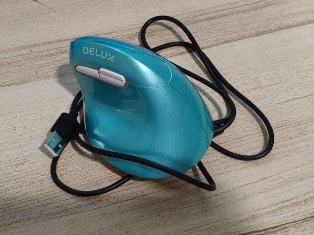 เมาส์ Delux M618mini สีฟ้าเขียว วางทับสายชาร์จ USB-C สีดำอยู่