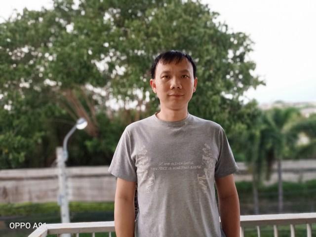 ภาพของผู้ใช้ใส่เสื้อยืดแขนสั้นสีเทา ยืนถ่ายอยู่ริมระเบียงบ้านชั้นบน เห็นแบ็กกราวด์เป็นต้นไม้อยู่นอกรั้ว