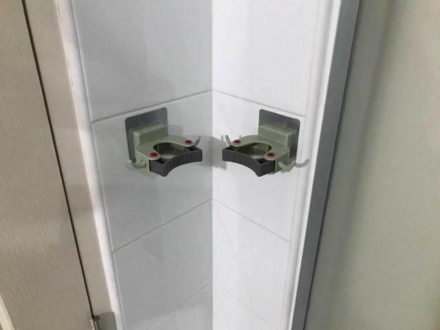 ที่แขวนไม้กวาดสองอัน ติดอยู่บนกำแพงห้องน้ำ