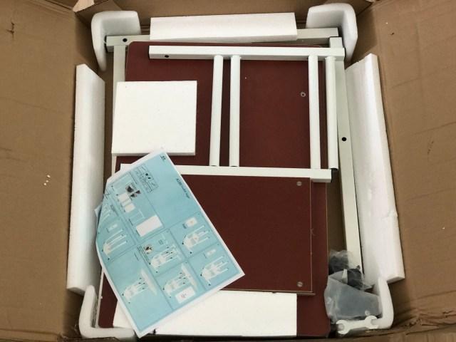 เปิดกล่องกระดาษที่บรรจุชิ้นส่วนต่างๆ สำหรับประกอบโต๊ะวางโน้ตบุ๊กข้างเตียง