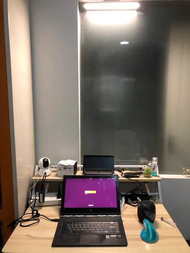 โต๊ะคอมพิวเตอร์ลายไม้ มีโน้ตบุ๊ก เมาส์ ลำโพงไร้สาย กล้องวงจรปิด และของจุกจิกวางอยู่บนโต๊ะ มีโคมไฟอ่านหนังสือไร้สายติดตั้งอยู่ตรงขอบกระจกด้านบน