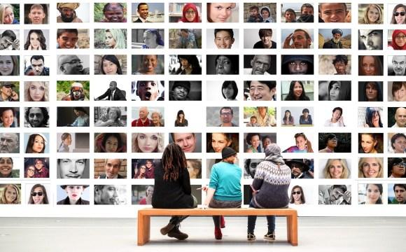 คนสามคนกำลังนั่งอยู่บนม้านั่ง ดูกำแพงที่เต็มไปด้วยภาพผู้คน