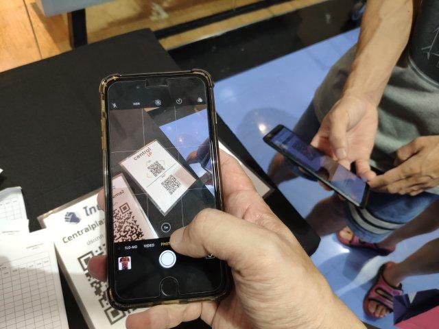 มือกำลังถือสมาร์ทโฟนเพื่อสแกน QR Code ที่วางไว้อยู่บนโต๊ะ