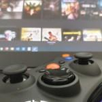 ภาพของจอยเกมคอมพิวเตอร์ วางอยู่บนโน้ตบุ๊ก โดยหน้าจอคอมพิวเตอร์มีการแสดงรายชื่อเกมพร้อมปกอยู่เป็นแบ็กกราวด์