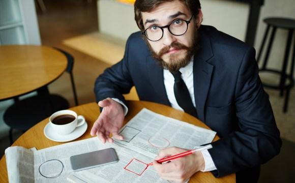 ผู้ชายไว้หนวดเครา ใส่แว่นตา กำลังหางานจากหน้าหนังสือพิมพ์ และวงตัวเลือกงานที่เขาสนใจ