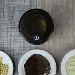 ภาพมุมสูงของเครื่องบดอเนกประสงค์ เห็นฝาปิดสีดำใส กับตัวอย่างของเมล็ดธัญพืชต่างๆ ที่ถูกบดแล้ว ได้แก่ ถั่ว กาแฟ และถั่วเขียว