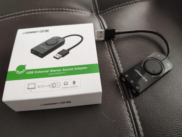 กล่องใส่อะแดปเตอร์การ์ดเสียง และ ตัวอะแดปเตอร์การ์ดเสียง USB ของ UGREEN วางอยู่บนเบาะหนังเทียมสีน้ำตาลเข้ม
