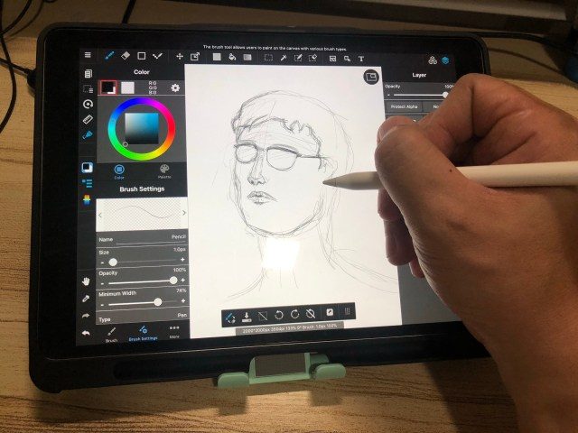มือกำลังจับ Apple Pencil วาดรูปอยู่ในแอปบน iPad Pro ที่วางอยู่บนขาตั้งแท็บเล็ตของ Choetech