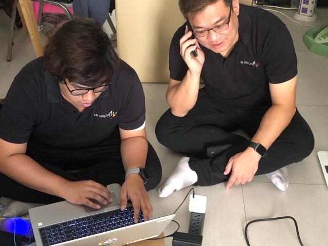 ทีมช่างเน็ตเวิร์กผู้ชำนาญสองคน ใส่เสื้อโปโลสีดำ และใส่แว่นตาทั้งคู่ กำลังนั่งเซ็ตระบบเน็ตเวิร์กอยู่ คนนึงกำลังใช้โน้ตบุ๊กอยู่ อีกคนกำลังคุยโทรศัพท์มือถืออยู่