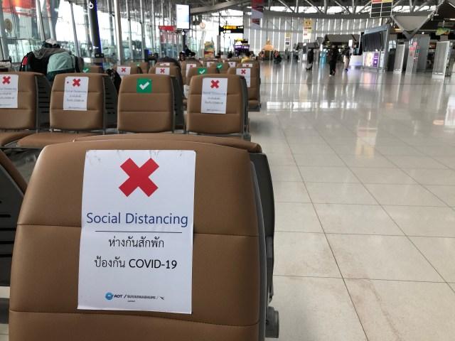 ที่นั่งในสนามบิน เก้าอี้บางตัวติดเครื่องหมายถูกสีเขียว คือ นั่งได้ และส่วนใหญ่เครื่องหมายกากบาท และเขียนว่า Social distancing ห่างกันสักพัก ป้องกัน COVID-19