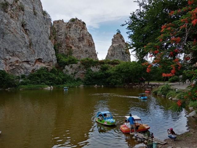 ทะเลสาบเล็กๆ ในอุทยานหินเขางู แบ็กกราวด์เป็นภูเขาหิน มีเรือถีบกำลังลอยอยู่บนทะเลสาบ 5 ลำ