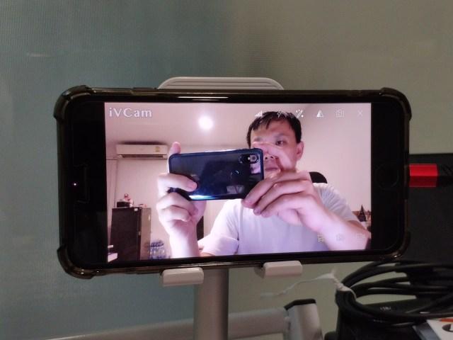 iPhone ที่เปิดแอป iVCam อยู่และกำลังแสดงภาพจากกล้องหน้า เป็นผู้ชายใส่เสื้อยืดคอกลมสีขาว กำลังยกสมาร์ทโฟนสีน้ำเงินถ่ายภาพอยู่