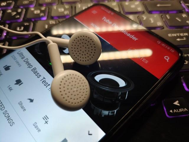 หูฟังแบบ Earbud กำลังวางอยู่บนตัวเครื่องสมาร์ทโฟน Huawei Y6P ที่กำลังเปิดแอป Tube Downloader อยู่