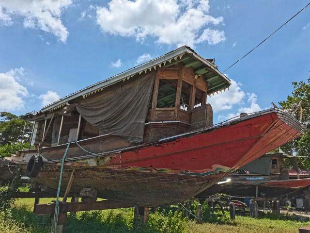ภาพเรือสีแดงส้ม ที่ถูกวางไว้อยู่บนแท่น ถ่ายด้วยเลนส์มุมกว้างปกติ