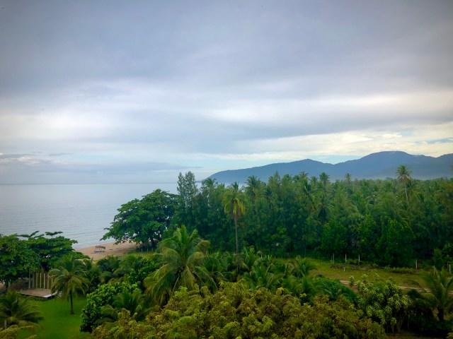 วิวจากระเบียงของห้องพักห้อง 612 ที่โรงแรมขนอมโกลเด้นบีช เห็นต้นไม้ สนามหญ้า หาดทราย ทะเล และแนวเทือกเขาอยู่ลิบๆ