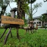 กวางไม้ตัวเล็กๆ 4 ตัว วางอยู่บนสนามหญ้าในโรงแรม La Flora Khao Lak ตัวที่อยู่ริมซ้ายสุด มีป้ายชื่อโรงแรมแขวนอยู่
