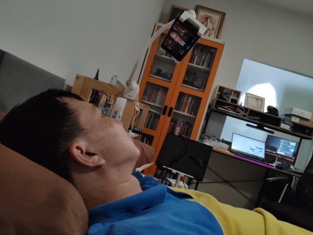 ผู้ชายใส่เสื้อโปโลเหลืองตัดน้ำเงินกำลังนอนอยู่บนเตียงดู YouTube ผ่านสมาร์ทโฟนที่ติดอยู่กับตัวจับสมาร์ทโฟนของ Choetech
