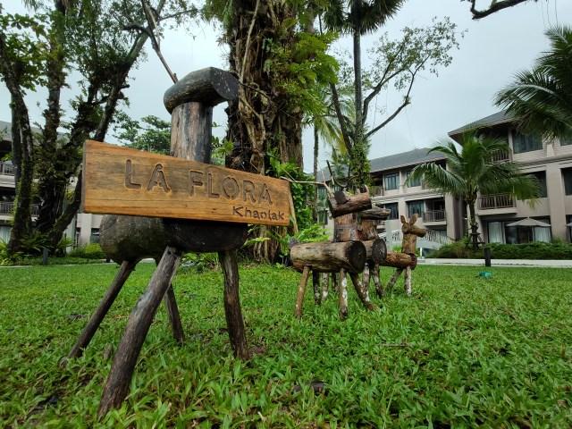 ตุ๊กตากวางทำจากไม้ แขวนป้าย La Flora Khaolak วางเรียงรายอยู่ในสวน มีตึกห้องพักอยู่ด้านหลัง