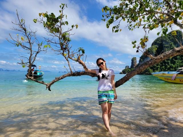 ผู้หญิงผมยาว ใส่กางเกงขาสั้น ยืนพิงกิ่งไม้อยู่ริมทะเล