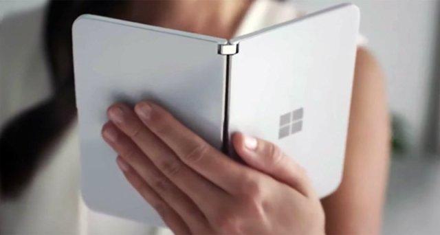 หญิงสาวกำลังถือและอ่านอีบุ๊กจาก Microsoft Surface Duo ที่อยู่ในมือ
